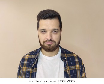 Portrait of a young European man in a checked shirt sad