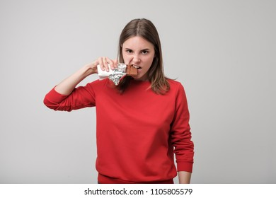 Portrait of young european woman eating chocolate in agressive mode. Having problem with diabetes and sugar level.