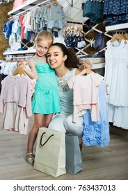 portrait of young european woman and girl shopping kids apparel in clothes store