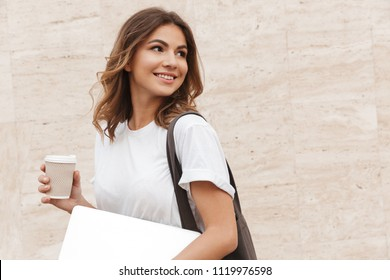 Portrait of young european woman walking against beige wall outdoor with silver laptop and takeaway coffee in hands