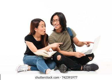 Portrait of a young excited asian students couple with backpack holding books and laptop while sitting and pointing finger away isolated over white background