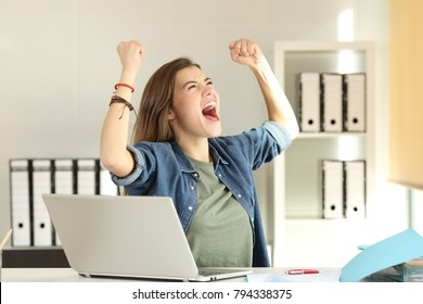 Portrait of a young excited intern celebrating success at office