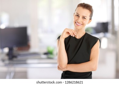 Portrait of a young executive businesswoman standing at office while smiling and looking at camera.