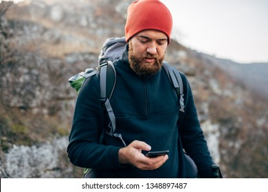 Portrait of young explorer bearded man trekking in mountains, using mobile phone for GPS application. Traveler man texting messages and browsing on Internet via his smart phone after hiking in moutain