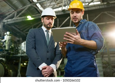 Portrait of young factory worker using digital tablet showing something to businessman wearing hardhat in workshop of modern plant, copy space
