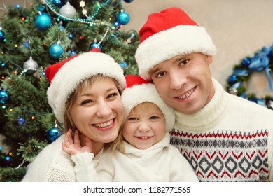 portrait of a young family celebrating Christmas at home. father, mother and child on the background of the Christmas tree. New Year and xmas people