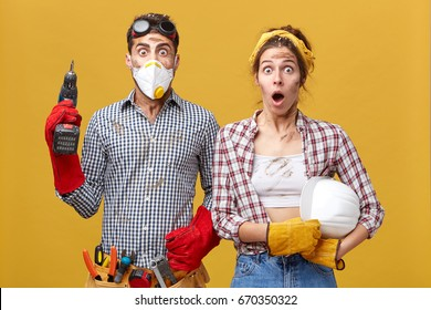 Portrait of young family couple wearing protective clothes while doing repearing in their appartment holding drill and hardhat having surprised look being frightened to do much work having dirty faces