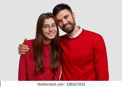 Portrait of young family European couple wear red clothes, pose for making common photo, have good relationships, warm cuddle, isolated over white studio background. People and relations concept