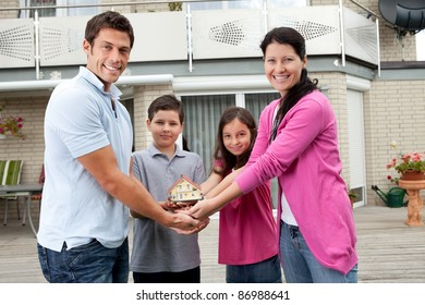 Portrait of young family of four holding a model of house - Outdoors