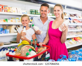 Portrait of young family which is selecting milk in supermarket.