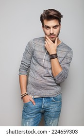 Portrait of a young fashion man holding his hand in pocket while fixing his beard, looking at the camera.