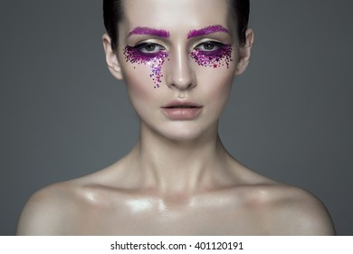 Portrait of young fashion model with beautiful makeup on grey background with sequins