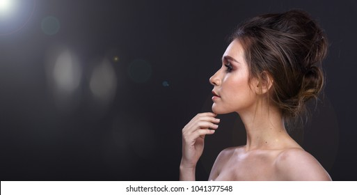 Portrait of Young Fashion Model caucasian Woman looking an idea and pointing to left side copy space area for text ads, Studio Lighting dark gray background