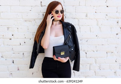 Portrait of a young fashion redhead woman outdoor, talking smart phone. Lifestyle outfit trendy black leather jacket and little bag