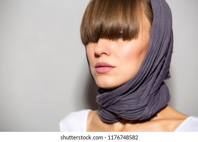 Portrait of young fashion woman wearing scarf and her fringe hiding her eyes