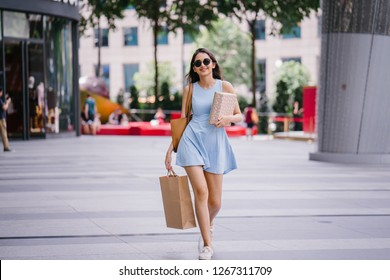Portrait of a young, fashionable and happy young Indian Asian woman in a blue dress and sunglasses walking down a street in the shopping district with her shopping bags.