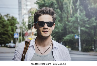 Portrait of young fashionable male dressed in white shirt, with smiling face against city street background, day, outdoor. Cheerful guy is walking around street. Discovering and travel city concept