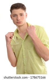 Portrait of a young fashionable man wearing a green shirt. Relaxed man standing holding his collar.