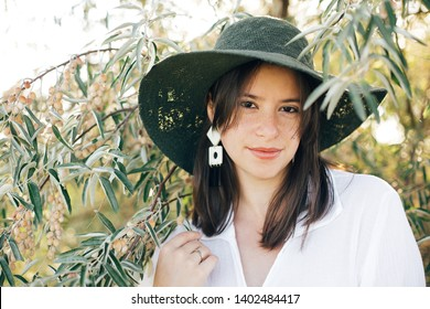 Portrait of young fashionable woman with modern earrings posing in  green olive branches in soft evening light, stylish boho girl in hat relaxing on tropical island. Summer vacation