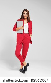 Portrait of a young fashionable woman in a red pantsuit and glasses