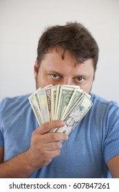 Portrait of young fat man holding money in his hand up to chin and close his face, isolated on white background