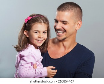 Portrait of young father carrying cute little daughter. Studio shot.