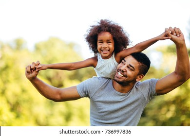 Portrait of young father carrying his daughter on his back - Shutterstock ID 736997836