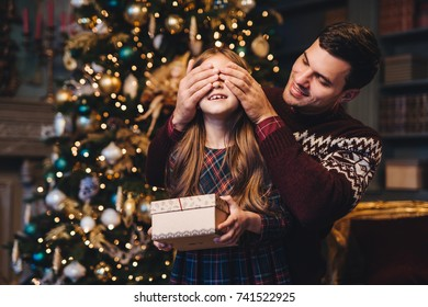 Portrait of young father covers his daughter`s eyes as going to make surprise for her, gives present, stand together near Christmas tree. Happy smiling girl receives gift from dad. Surprise concept