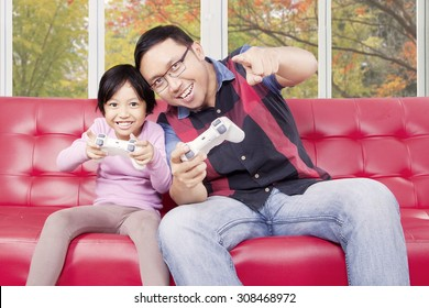 Portrait of young father playing video game with his daughter while sitting on the sofa at home