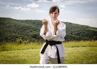 Portrait of young female athlete wearing kimono and doing karate blows outdoors. Martial arts.