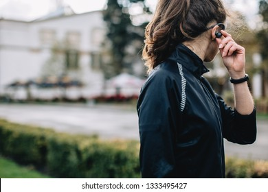 Portrait of young female athlete wearing sport jacket listening portable music player outdoors during the training session in the morning