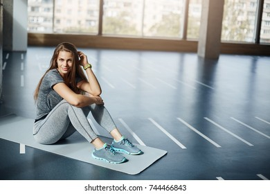Portrait of young female body fitness trainer or coach sitting in empty gym before a group workout. Fitness concept.