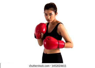 Portrait of a young female boxer in a fighting stance on white isolated background. Young Asian woman doing boxing exercise with serious look.