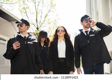 Portrait Of Young Female Celebrity With Bodyguards Walking On Sidewalk