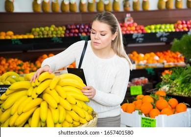 Porträt junger Frauen, die frische Bananen im Supermarkt auswählen