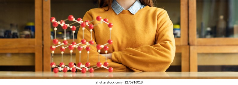 Portrait of young female college student in chemistry class. Focused student in classroom. Authentic Education concept.