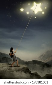 Portrait of young female college student taking stars from the sky space