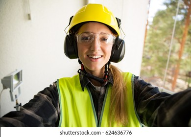 Portrait of a Young Female construction worker in hard hat drilling concrete wall with a drill and smiling at the camera. Building and renovation. feminism concept. Selfie