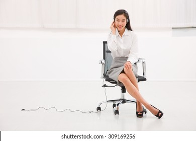 Portrait of a young female customer service executive sitting chair