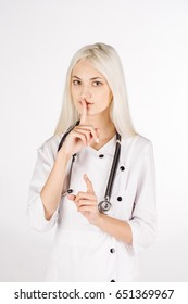 portrait of a young female doctor doing shush gesture as silence or secret, isolated on white background
