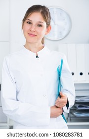 Portrait of young female doctor in lab coat holding clipboard with medical records