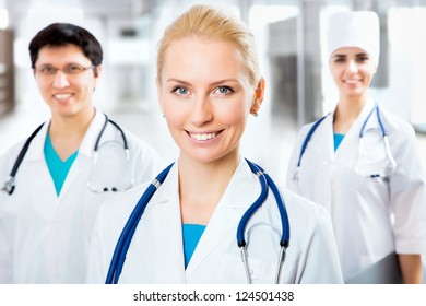 Portrait of a young female doctor sitting in front of his team and smiling
