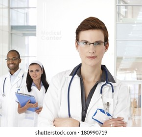 Portrait of young female doctor and team at medical center.