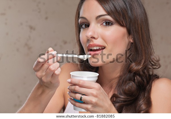 Portrait of young female eating yogurt