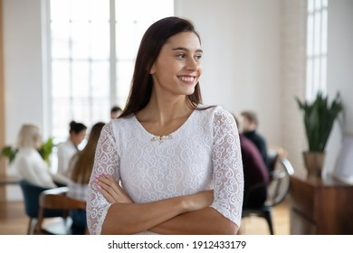 Portrait of young female employee in casual wear poses for camera in modern office with colleagues on background. Happy student looking away, dreaming, smiling. Corporate business picture concept