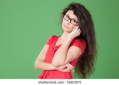 Portrait of young female in eye-glasses talking on phone isolated on chroma-key background