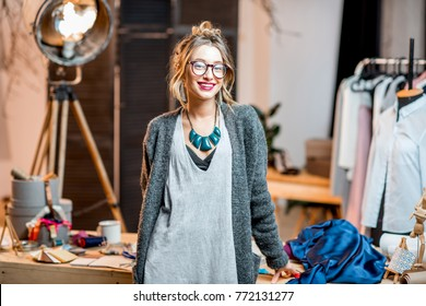 Portrait of a young female fashion designer standing at the office with different tailoring tools and clothes