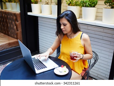 Portrait of a young female freelancer using laptop computer for distance job while sitting in modern coffee shop interior, smart brunette woman working on net-book during morning breakfast in cafe bar