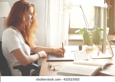 Portrait of young female freelancer working at home using digital tablet. Redhead woman designer in white T-shirt hand drawing on graphic tablet while sitting in front of computer screen. Flare sun