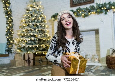 Portrait of young female girl with curly hairstyle smiling, looking at camera and sitting in cozy room with Christmas tree